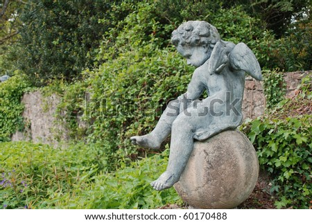 little cupid angel with spreaded wings on a concrete ball in an irish garden