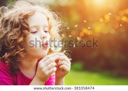 Little curly girl blowing dandelion. Foto stock ©