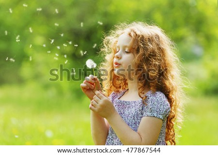 Stock Photo Little curly girl blowing dandelion.