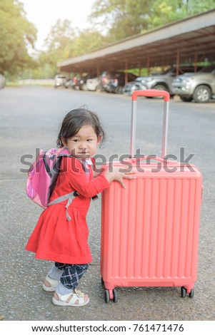 Little curly hair asian baby girl with backpack carries heavy luggage packed in apparent readiness to travel. vacations, holiday, travel and lifestyle concept. #761471476