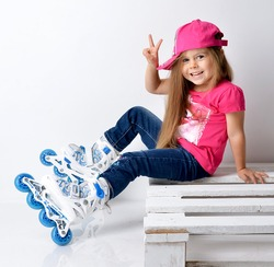 Little curly hair baby girl kid sitting with roller skates in pink tshirt and hat happy smiling and showing peace sigh
