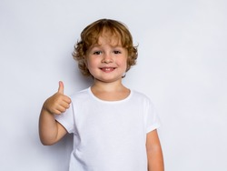 little curly redheaded boy in a white t-shirt showing thumbs up,  ok sign