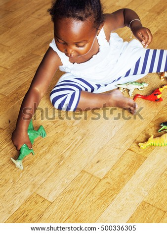 little cute african american girl playing with animal toys at ho #500336305