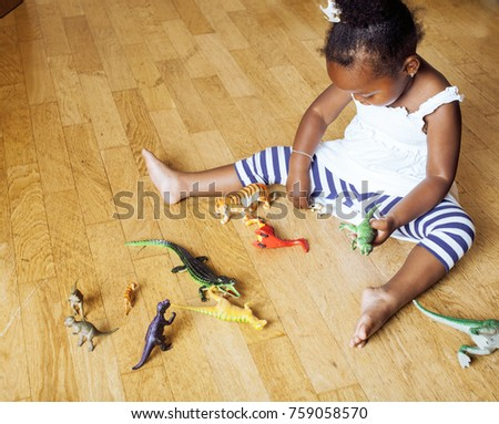 little cute african american girl playing with animal toys at home, pretty adorable princess in interior happy smiling, lifestyle people concept close up #759058570