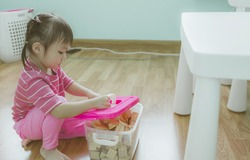 Little cute asian girl daughter picking up toys after playing at home. Copy space.