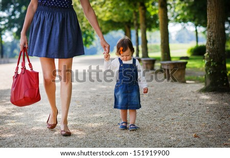 Little cute baby girl walking with beautiful mother in summer park