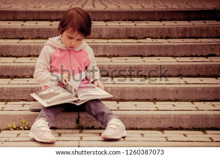 Little cute baby girl watching a book (Science, education, knowledge, self-improvement, success)