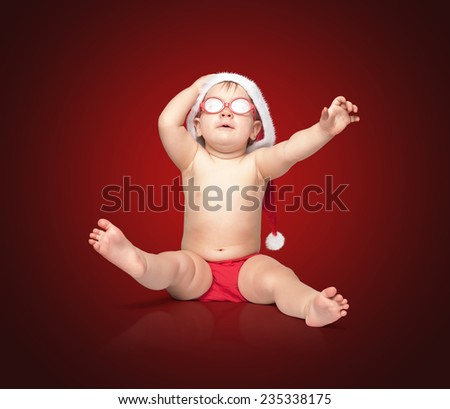 little cute baby in red Santa hat and red glasses barely holds his hat, surprise! sits on a colored background. #235338175