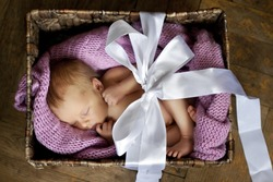 little cute baby in the box with a gift bow