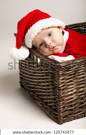 little cute baby with santa costume lying in basket