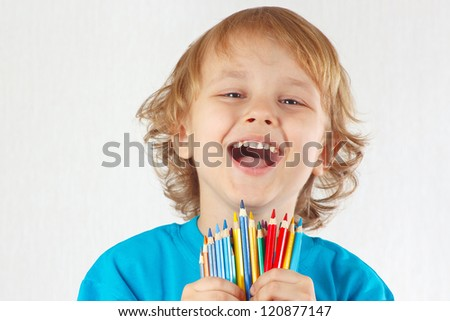 Little cute blond boy holds color pencils on a white background