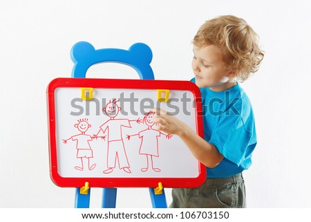 Little cute blond boy shows his family painted on a whiteboard