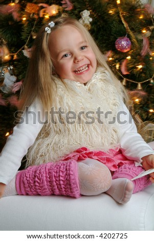 Little cute blond girl in front of christmas tree.