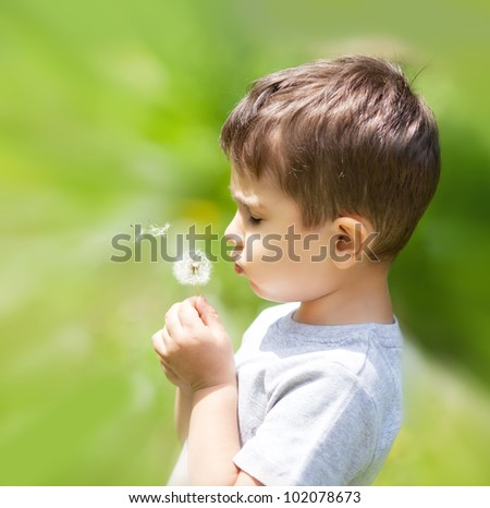 Little cute boy blowing dandelion on blurred nature background