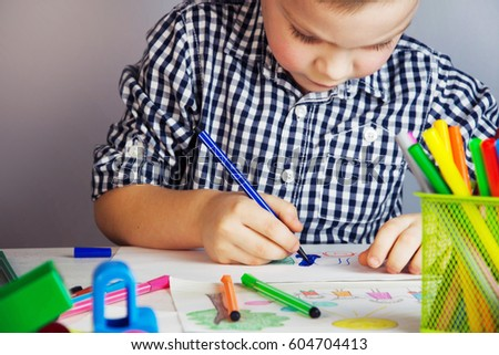 Little cute boy draws with color pencils. #604704413