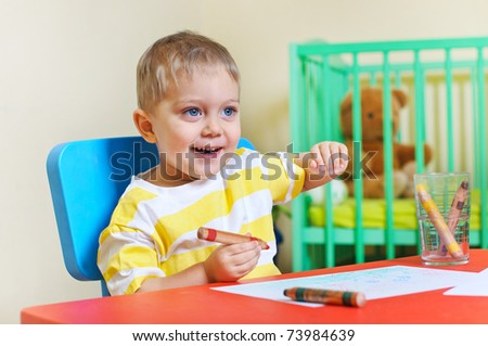 Little cute boy draws with crayons in the nursery