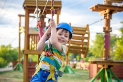 Little cute boy enjoying activity in a climbing adventure park on a summer sunny day. toddler climbing in a rope playground structure. Safe Climbing extreme sport with helmet insurance motion blurred