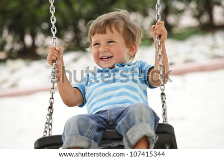 Little cute boy having fun on chain swings