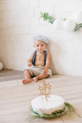 Little cute boy in suspenders and vintage cap. First birthday with a birthday cake and decor with white balloons and sprigs of eucalyptus. Rustic First Birthday Party