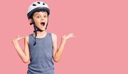 Little cute boy kid wearing bike helmet celebrating victory with happy smile and winner expression with raised hands