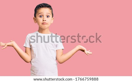 Little cute boy kid wearing casual white tshirt clueless and confused expression with arms and hands raised. doubt concept.