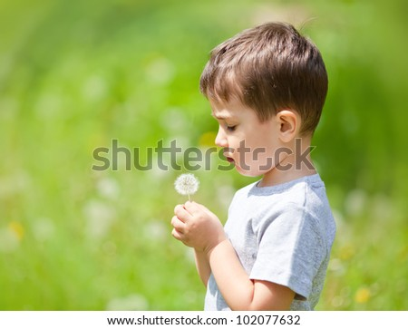 Little cute boy looks on dandelion on blurred nature background