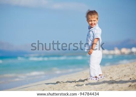 Little cute boy on the beautiful exotic white beach, Mallorca, Spain