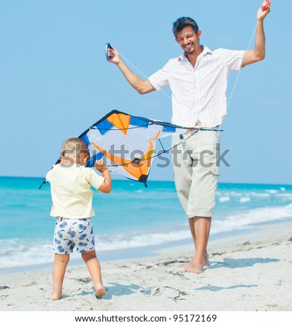 Little cute boy playing his father with a colorful kite on the tropical beach. - stock photo