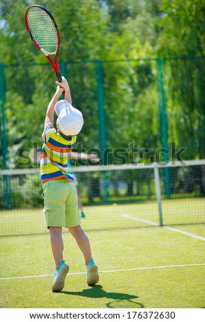 Little cute boy playing tennis on green court