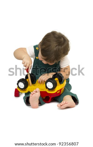 Little cute boy playing with a plastic toy truck.