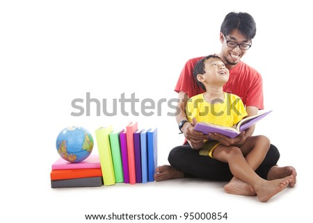 Little, cute boy reading a book with his father