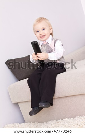 Little cute boy sitting on the sofa with remote control
