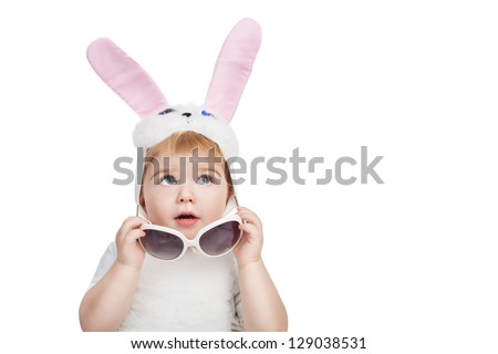 Little cute boy with big blue eyes dressed in Easter bunny ears take off sunglasses and looking up. Little Easter bunny on white background.