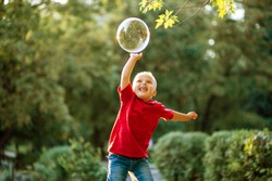 Little cute boy with Down Syndrome plays with huge soap bubbles in the park, a disabled child wants to burst a soap ball, caring for sick people, genetic disease, lifestyle.
