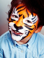 little cute boy with faceart on birthday party close up, little cute tiger, lifestyle people concept