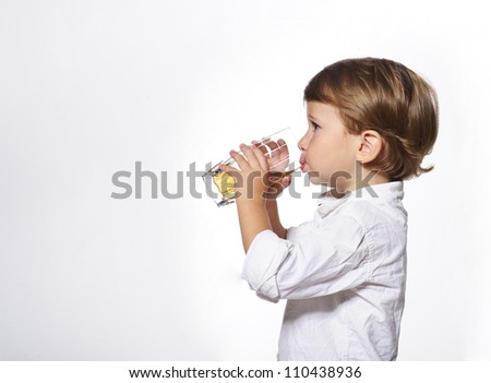 Little cute boy with glass of apple juice in white background.