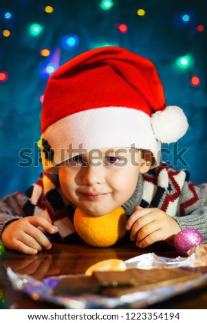 Little cute boy with santa hat. In the background bright festive lights. Little Cute Boy Cute Boy holding orange Fruit orange Fruit #1223354194