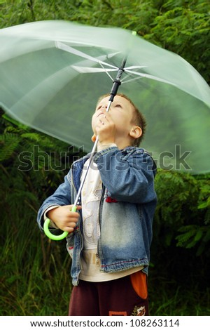 Little cute boy with spinning umbrella