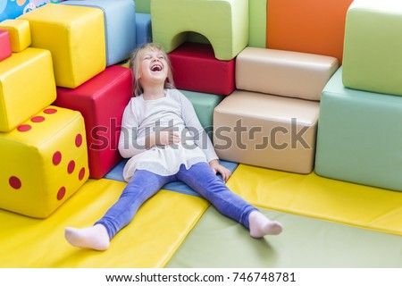 Little cute caucasian blond girl die laughing while playing with soft building blocks at indoor playground.