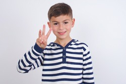 little cute Caucasian boy kid wearing stripped t-shirt against white wall showing and pointing up with fingers number three while smiling confident and happy.