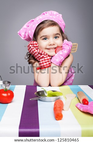 little cute chef holding wooden spoon with different pair of gloves looking at camera and smiling on gray background