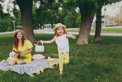 Little cute child baby girl with basket play and have fun, rest with woman in yellow clothes on green grass in park. Mother, little kid daughter. Mother's Day, love family, parenthood, childhood