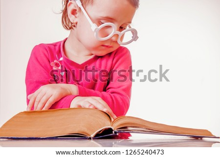 Little cute child girl watching a book. Science, education, knowledge, self-improvement concept.