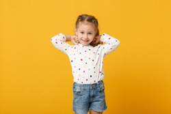 Little cute child kid baby girl 4-5 years old wearing light denim clothes isolated on pastel yellow wall background, children studio portrait. Mother's Day, love family, parenthood childhood concept