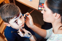 little cute child making facepaint on birthday party, zombie Apocalypse facepainting, halloween preparing concept, lifestyle people