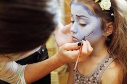 little cute child making facepaint on birthday party, zombie Apocalypse facepainting, halloween preparing