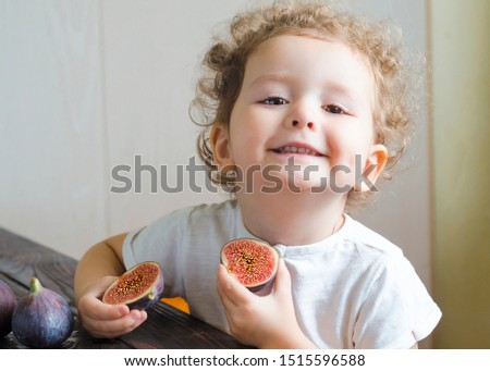 Little cute contented smiling girl holds figs halves in her hands. child with fig. kid with ripe juicy ripe fruit. healthy snack, proper nutrition, vegetarianism, vitamins, autumn harvest.