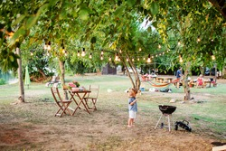 Little cute curly boy in summer jeans shirt and white shorts standing at family camping with picnic, bench, camp fire and garden lights