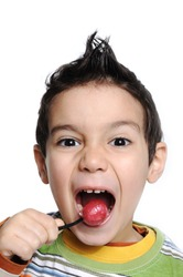 Little cute funny boy with colorful lollipop candy