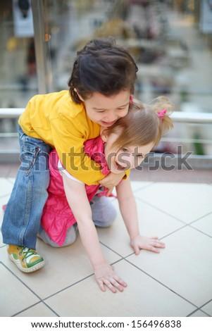 Little cute girl and boy play on floor in big mall. Boy saddled girl. Focus on girl.